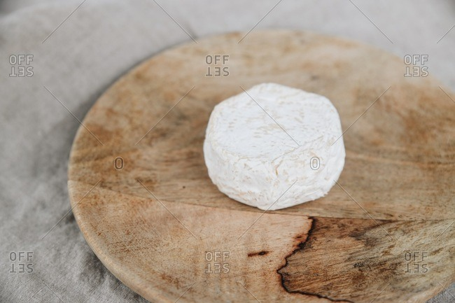 Soft white bloomy rind cheese wheel on a wooden cutting board