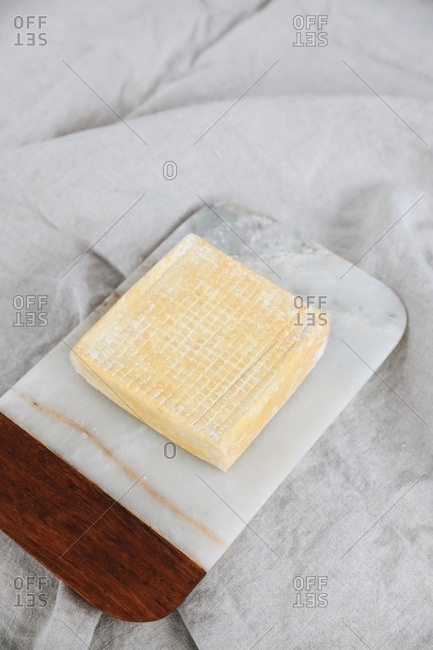 A square shaped bloomy rind cheese on marble cutting board