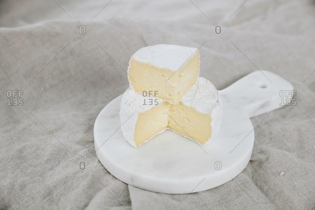 Soft bloomy rind cheese wheel cut on marble