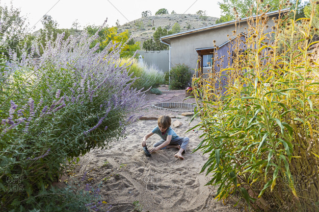 7 year old boy playing in sandy garden with his toy ship.