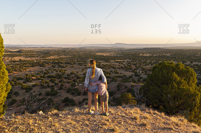 Teenage girl embracing her younger brother in the Galisteo Basin, Santa Fe