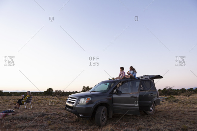 Teenage girl and her younger brother sitting atop their SUV at sundown.