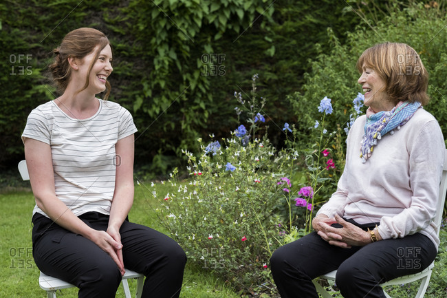 Woman and female therapist seated at an alternative therapy session in a garden.