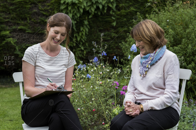 Woman and female therapist at an alternative therapy session in a garden.