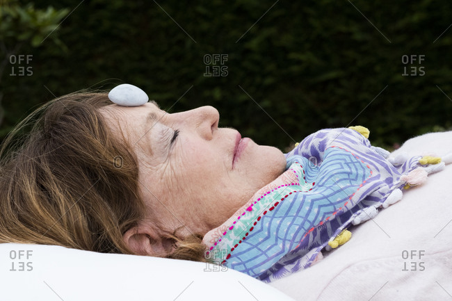 Woman with stone on her forehead during alternative therapy session in a garden.