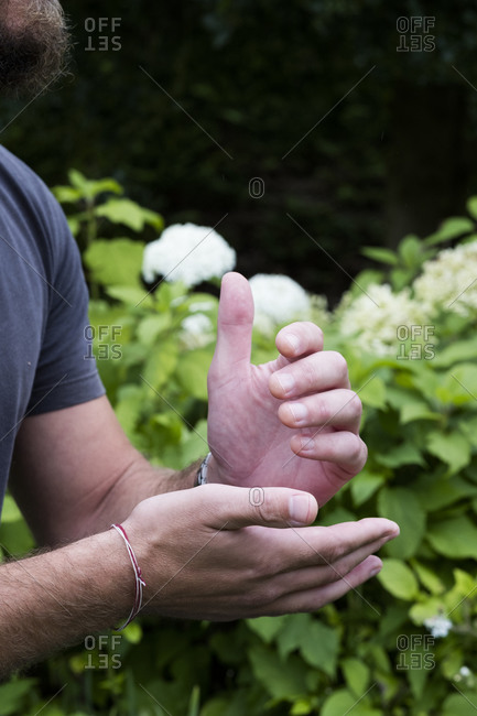 Close up of a man's hands, together and pressing meridian points on the hands, therapy