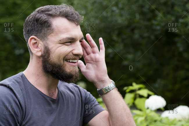 Man sitting in garden during alternative therapy session, touching his head.