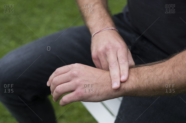A man seated, two fingers on his opposite wrist, EFT touching therapy