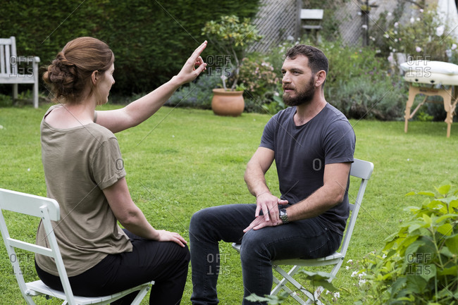 Therapist and client seated in a garden, woman with her hand raised and two fingers extended.