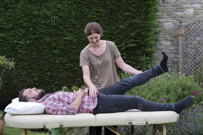 Man on a couch and therapist raising his leg, in a garden therapy session