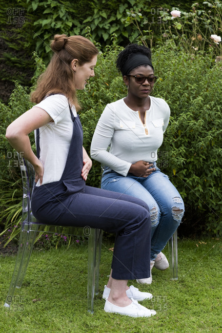 Woman and female therapist mirroring each other, hands on back and stomach