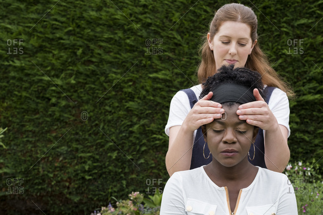 Therapist with her hands on a client's temples, outdoor therapy session