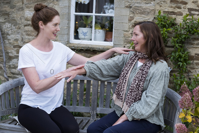 Therapist and client seated in a garden, touching the hands and shoulder.