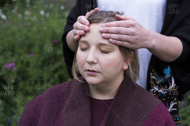 Therapist using both hands touching the top of a client's head.