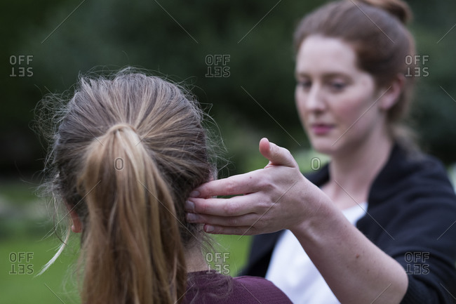 A therapist touching a client's head by her ear.