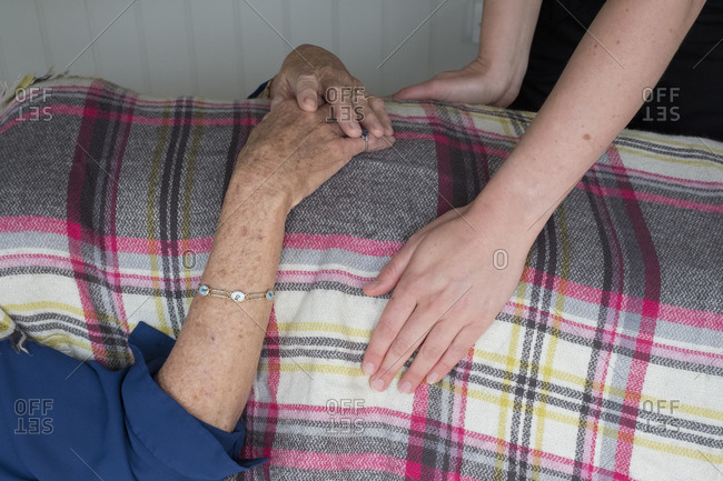 Woman on a couch a therapist placing hands on her head and stomach,