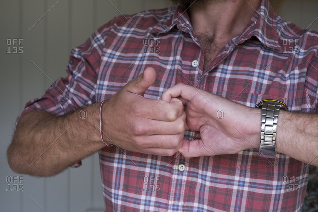 Man with hands clasped gripping the curled fingers.