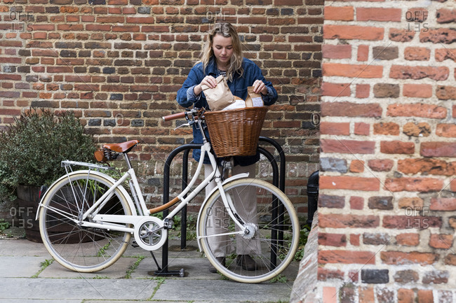 Young blond woman wearing face mask standing next to bicycle, arranging paper shopping bags in basket.