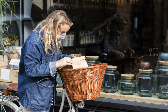 Young blond woman wearing face mask with bicycle, standing outside waste free wholefood store.