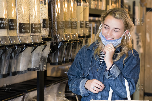 Young blond woman wearing face mask, shopping in waste free wholefood store.