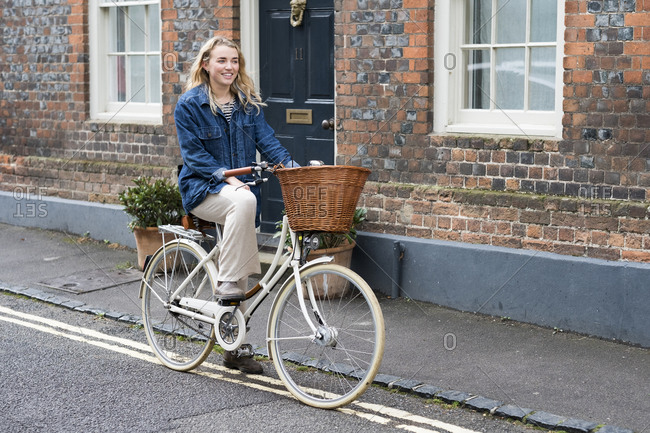 Young blond woman cycling down a village street.