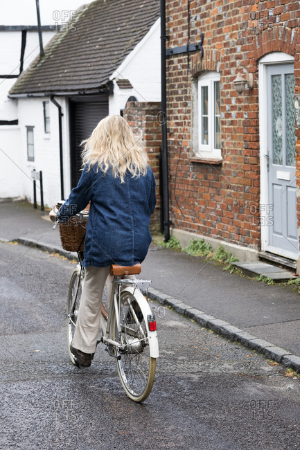 Rear view of young blond woman cycling down a village street.