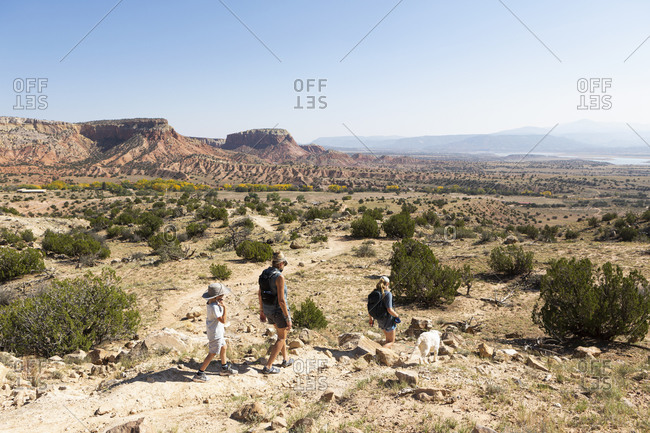 Three people, family hiking on a trail through a protected canyon landscape