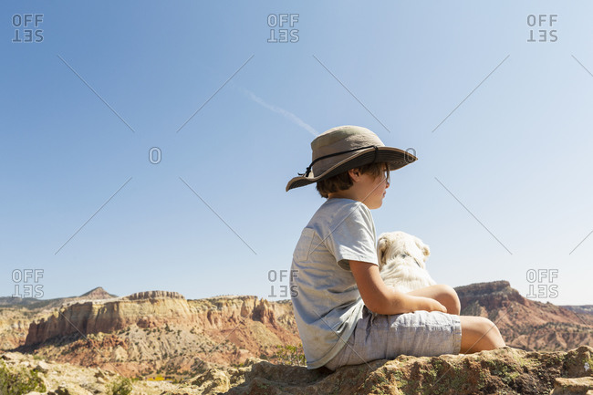 young boy sitting on rock with his dog