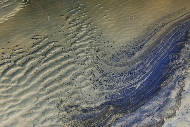 Ocean water and ripple patterns in the sand at low tide.