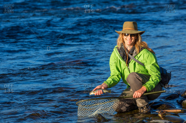 Fly fisherwoman landing trout with net on river, British Colombia, Canada.