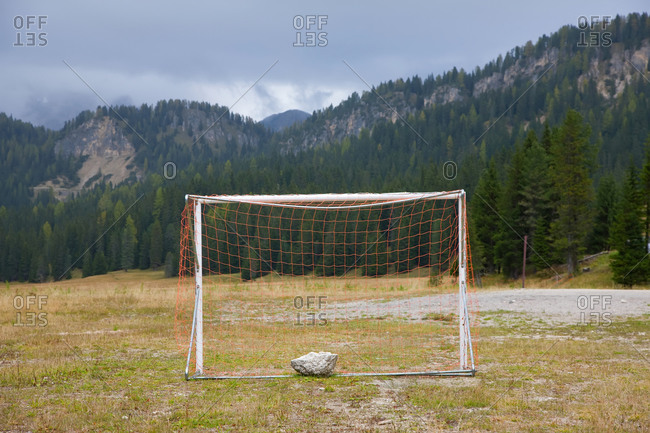 Soccer goal and a flat field in a valley in the Dolomites.