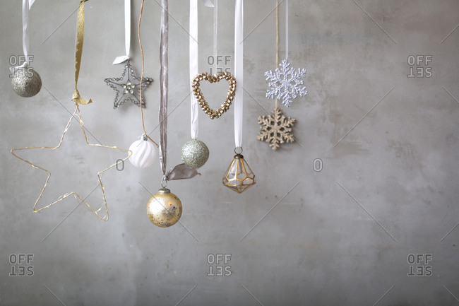 Christmas decorations, close up of silver, white and golden Christmas baubles on ribbons on grey background.