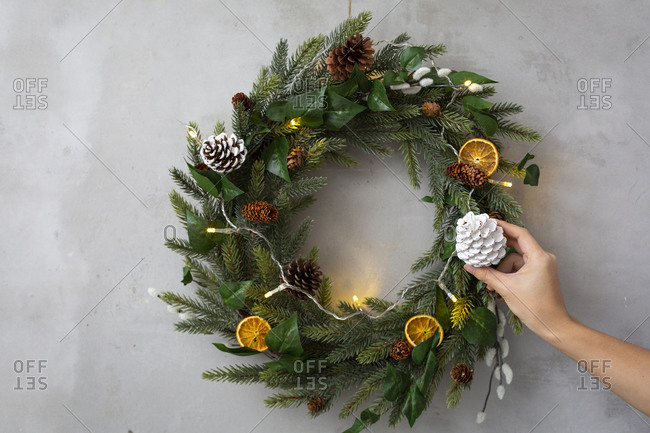 Christmas decorations, close up of person decorating Christmas wreath with ornaments.