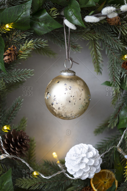 Christmas decorations, close up of golden bauble and  white pine cone on Christmas wreath.