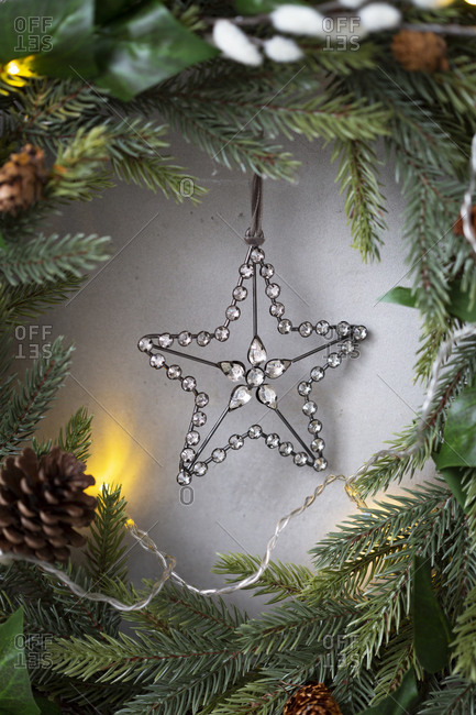 Christmas decorations, close up of silver star on Christmas wreath.