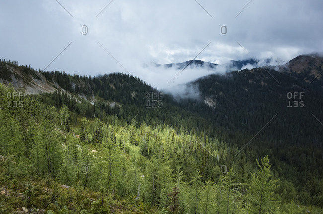 Storm clouds lifting over remote mountain range and alpine meadow