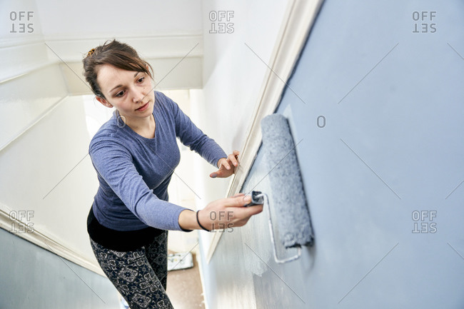 Woman using paint roller to paint staircase