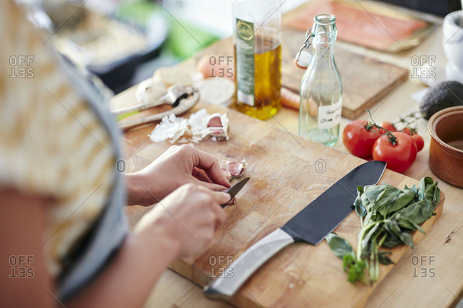 Woman in kitchen preparing garlic for cooking on chopping board