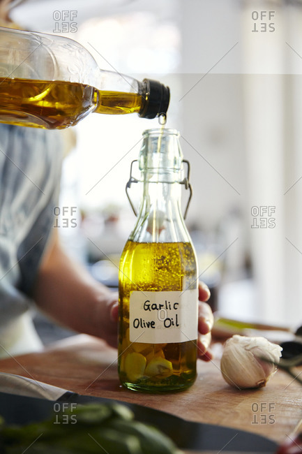 Woman pouring olive oil into bottle containing garlic