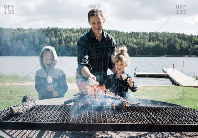 Father toasting marshmallows with his kids at the beach on a bbq