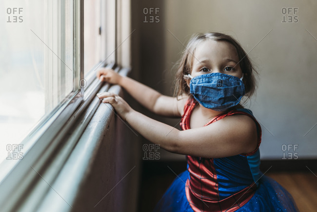 Preschool age girl by window in Halloween costume and face mask