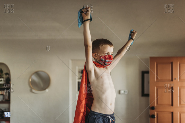 Young boy with arms outstretched wearing superhero costume and mask