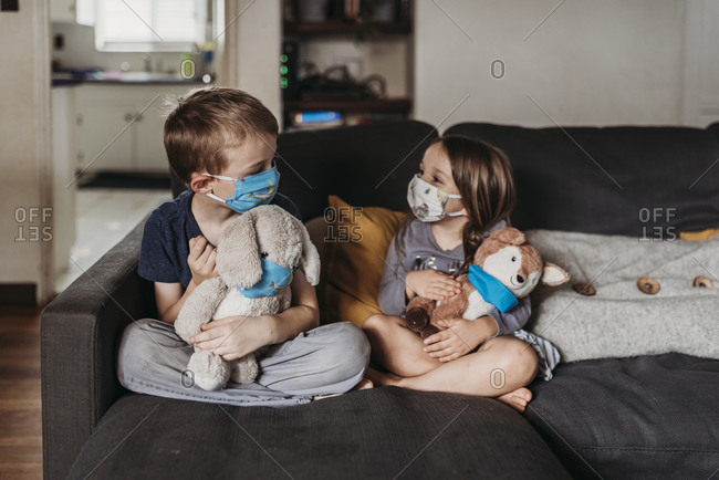 Preschool age girl and school age boy with masks sitting on couch