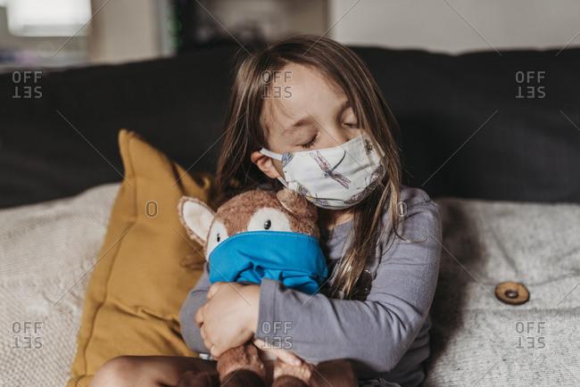 Preschool age girl with mask on cuddling stuffed animal with mask