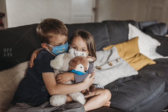 Young girl and school-age boy with masks hugging and smiling on couch