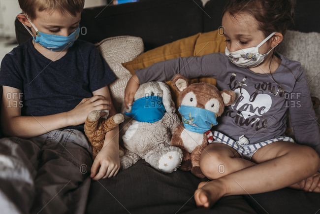 Young girl and young boy with masks playing with animals on couch