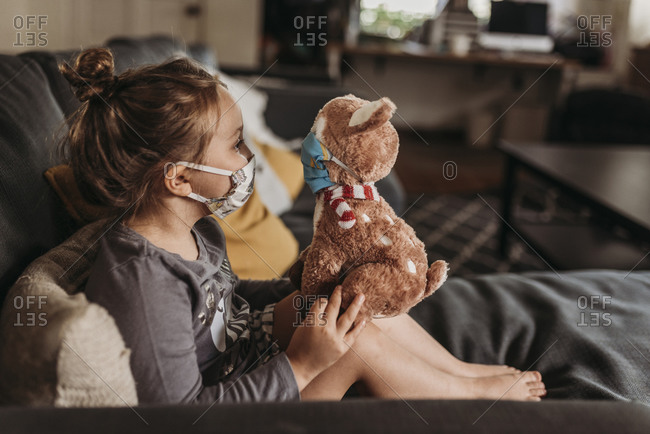 Side view of preschool age girl with mask on cuddling masked animal
