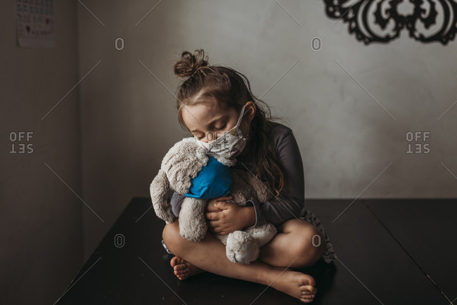 Young girl with mask on cuddling with masked stuffed animal