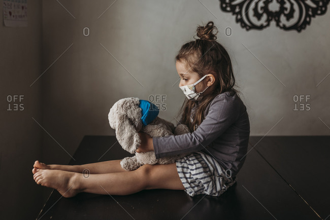 Side view of young girl with mask on sitting with masked animal