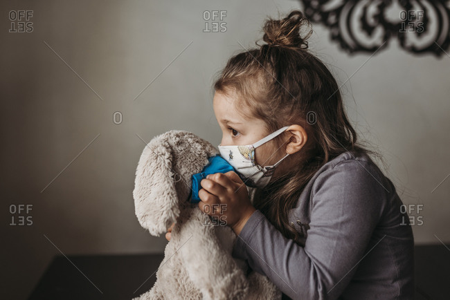 Close up of young girl with mask on kissing masked stuffed animal